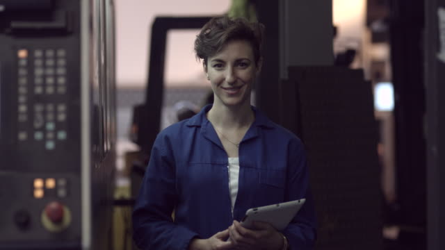 ms_portrait of female worker at steel plant, holding digital tablet - occupazione industriale video stock e b–roll