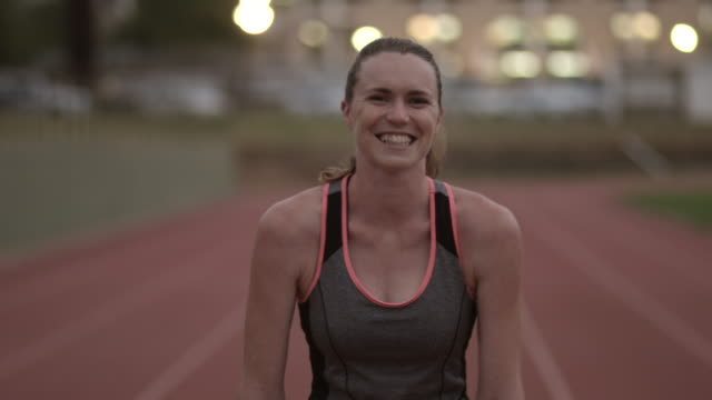 ms_portrait of smiling female track athlete at stadium - athlete stock videos & royalty-free footage