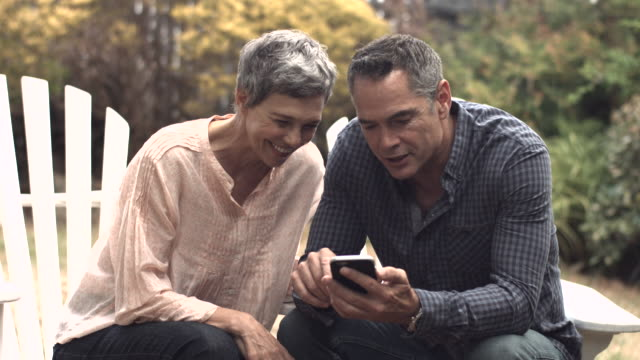 MS_Senior couple looking at smartphone together in garden