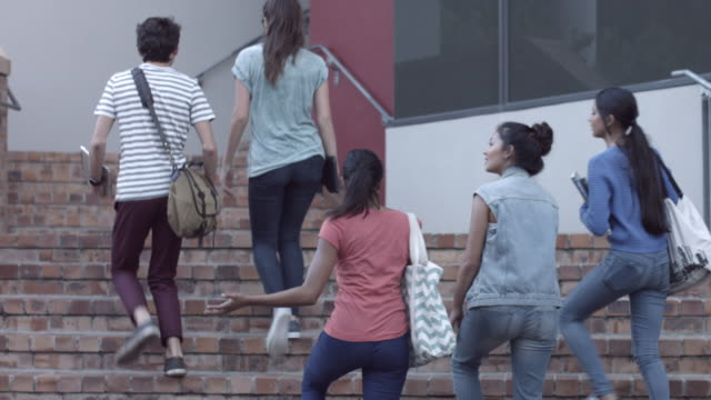 ms_students walking out of school building, holding books and tablets - female high school student stock videos & royalty-free footage