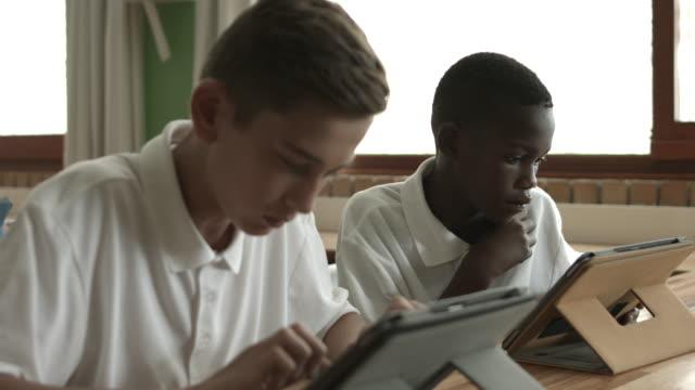 ms_two schoolkids working on digital tablets in classroom - schulkind nur jungen stock-videos und b-roll-filmmaterial