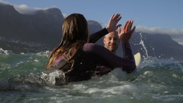 vídeos de stock, filmes e b-roll de ms_two surfers doing high five in the water - high five