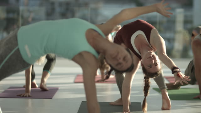 ms_yoga class doing stretching exercises, in rooftop studio - yogastudio stock-videos und b-roll-filmmaterial