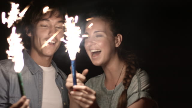 ms_young couple playing with sparklers and laughing - long hair stock videos & royalty-free footage