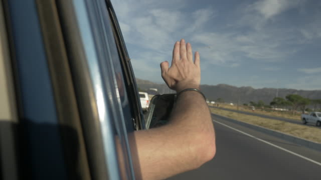 ms_young man making waves with the hand out of car window - winken stock-videos und b-roll-filmmaterial
