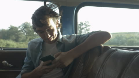 vídeos de stock e filmes b-roll de ms_young man typing on smartphone, on back seat of old car - young men