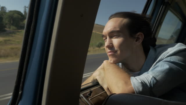 vidéos et rushes de ms_young man with wind in the hair, enjoying the sunset from the backseat of old car - air vehicle