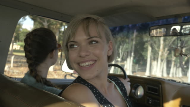 MS_Young woman laughing with friends in big old car