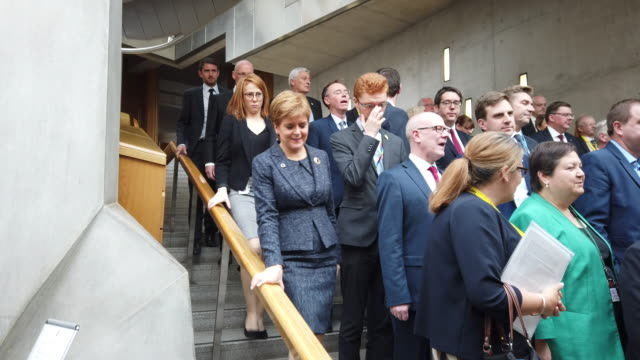 msps flood down the main staircase of the scottish parliament to the garden lobby following first minister's questions before gathering for a charity... - holyrood bildbanksvideor och videomaterial från bakom kulisserna
