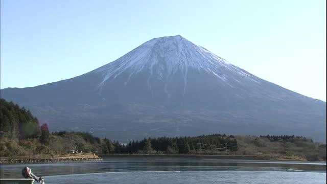 mt. fuji looms over icy lake tanuki. - shizuoka prefecture stock videos and b-roll footage
