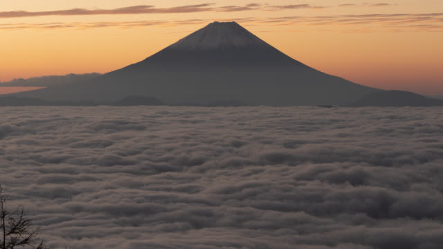 mt. fuji over a sea of clouds (time lapse/zoom in) - 胸を打つ点の映像素材/bロール