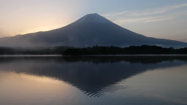 mt. fuji reflected in lake tanuki at dawn with ripples on the water surface - light natural phenomenon stock videos & royalty-free footage