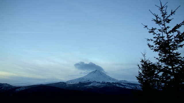 Mt. Hood in winter snow covered mountain and forest at dusk sunset
