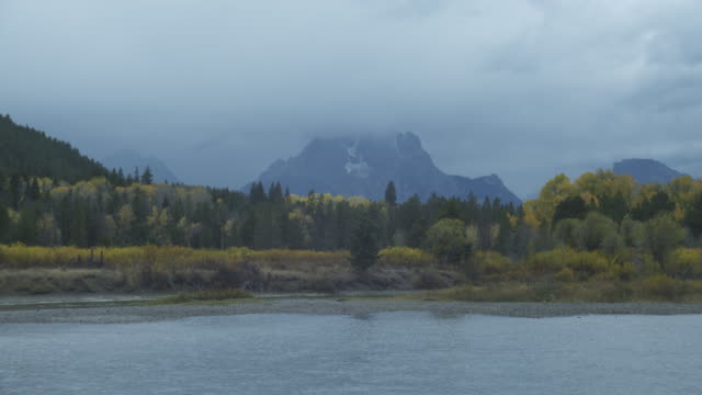 mt. moran looms in the distance beyond a lake in grand teton national park. - mt moran stock videos & royalty-free footage