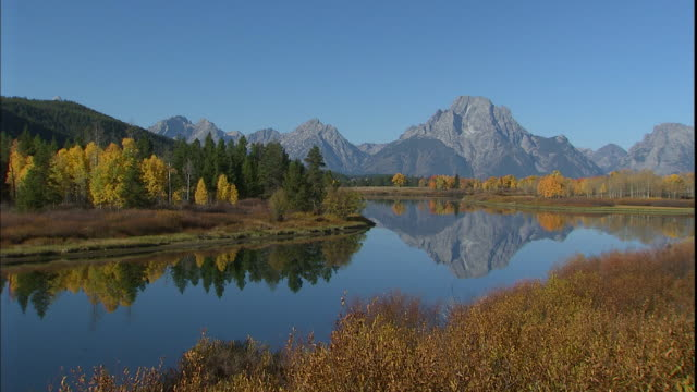 mt. moran reflects in the oxbow bend of the snake river in grand teton national park. - mt moran stock videos & royalty-free footage