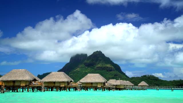 vídeos de stock e filmes b-roll de mt otemanu overwater bungalows aquamarine lagoon bora bora - territórios ultramarinos franceses