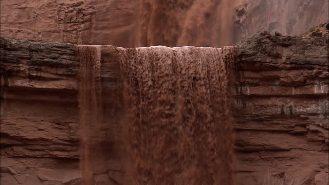 mud and water from a flash flood pour over a cliff in the grand canyon. - 自然災害点の映像素材/bロール