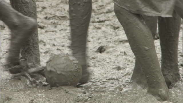 Mud covers the feet and legs of children playing football in a field. Available in HD.