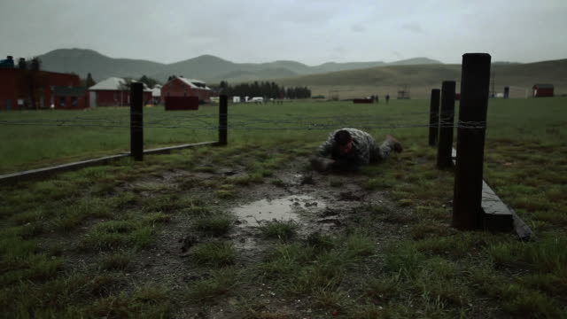 muddied soldiers crawl in an obstacle course - practice drill stock videos & royalty-free footage