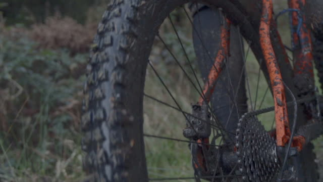 Muddy details of a man mountain biking in the woods. - Super Slow Motion - filmed at 240 fps