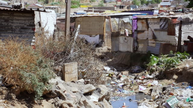 vidéos et rushes de ms muddy ditch with garbage between houses and shacks / diepsloot, south africa - cahute
