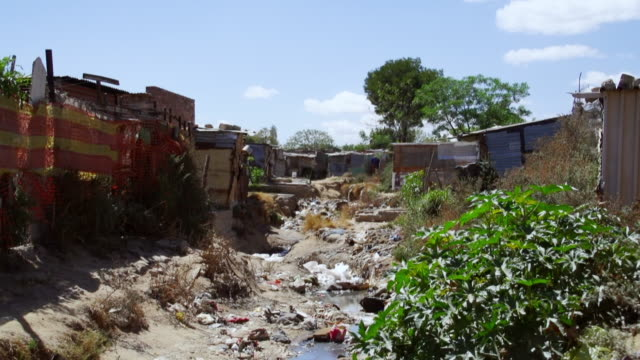 vidéos et rushes de ws muddy ditch with garbage between houses and shacks / diepsloot, south africa - cahute