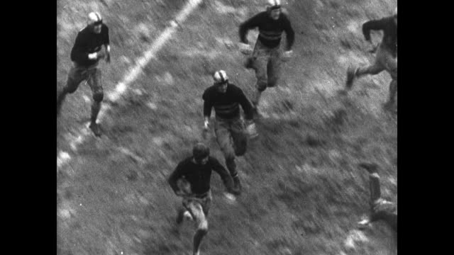 stockvideo's en b-roll-footage met muddy football game game play: #10 running tackled sliding in mud. different game: male cheerleaders flipping. cartoon: yale player 'did it for god... - 1936