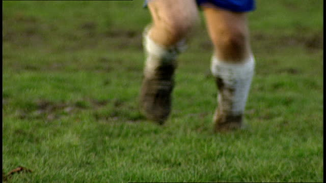 vídeos de stock e filmes b-roll de cu muddy legs playing soccer in brentford uk - barro