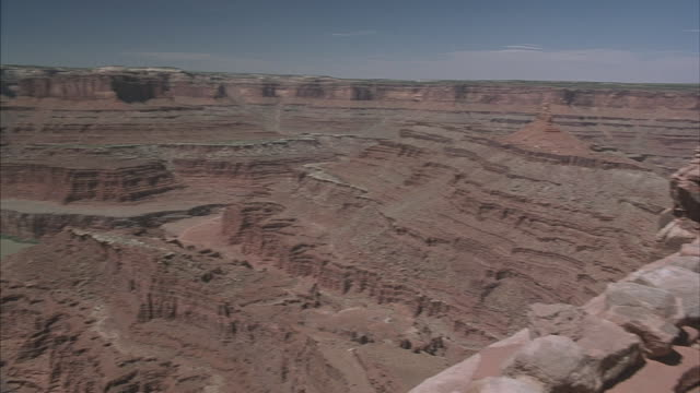 vidéos et rushes de a muddy river lies at the bottom of a spectacular canyon. - couches superposées