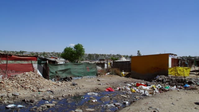 vidéos et rushes de ws muddy road between houses and shacks in town / diepsloot, south africa - cahute