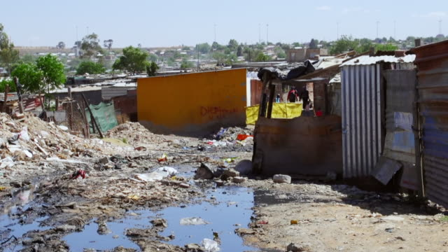 vidéos et rushes de ws muddy road between housing and shacks in town / diepsloot, south africa - cahute