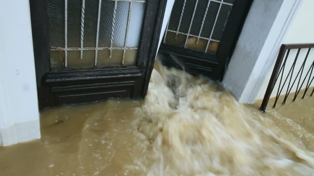 muddy water pouring through the entrance door - doorway stock videos & royalty-free footage