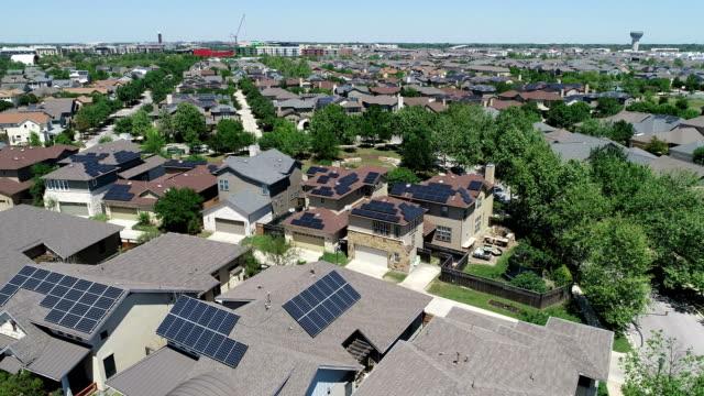 vídeos y material grabado en eventos de stock de suburbio de desarrollo nuevo de mueller con paneles solares de azotea en austin, texas - vista aérea - pájaros volando y paneles solares en la comunidad verde - tejado
