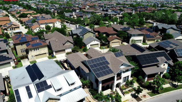 mueller new development suburb with rooftop solar panels in austin , texas - aerial view - lowering down - roof stock videos & royalty-free footage