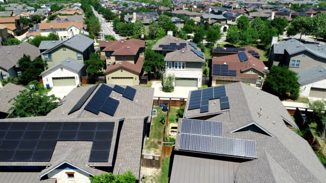 mueller new development suburb with rooftop solar panels in austin , texas - aerial view - orbiting around solar rooftops - sole video stock e b–roll