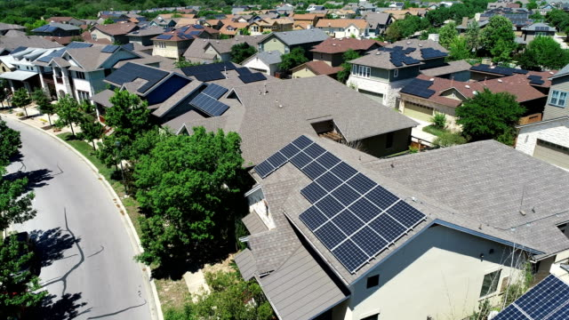 vídeos de stock e filmes b-roll de mueller new development suburb with rooftop solar panels in austin , texas - aerial view - backing up right above solar rooftops perfect - painel solar