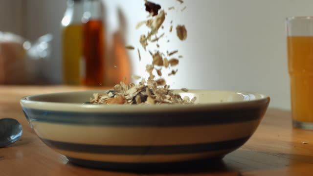 CU SLO MO Muesli being poured into bowl / Manchester, United Kingdom