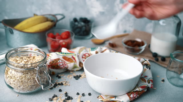 vidéos et rushes de bol de muesli aux bleuets frais, fraises et lait : ajout de céréales - bol et saladier