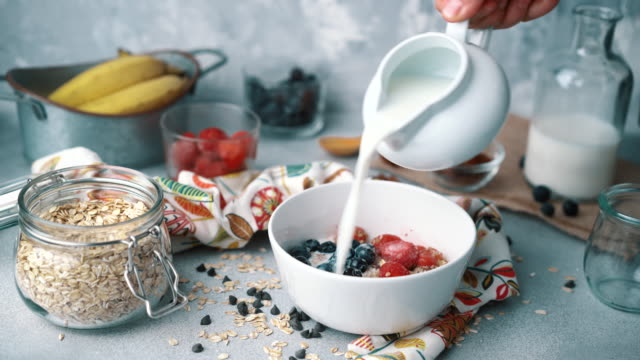 muesli bowl with fresh blueberries, strawberries and milk: pouring milk - cereal stock videos & royalty-free footage
