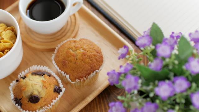 マフィン ケーキや gen 木製皿にブラック コーヒー朝食食材セットし、木製のテーブル、ドリー ショット右へ左 - マフィン点の映像素材/bロール