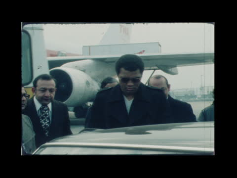muhammad ali at london airport; england: london: lap : ext muhammad ali poses with veronica porché ali : press; pan ali: ali and wife into car: - itv news at one stock videos & royalty-free footage