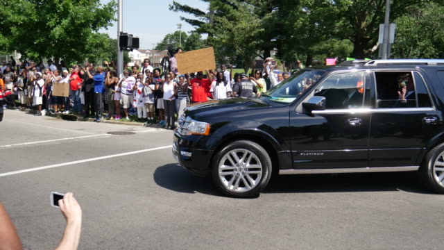 muhammad ali fans and mourners cheer as will smith passes by in a limousine while ali's funeral procession passes at 9th street and muhammad ali... - limousine luxuswagen stock-videos und b-roll-filmmaterial