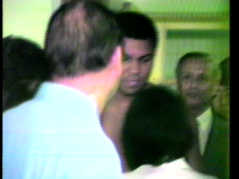 Muhammad Ali meeting fans waiting in corridor kissing woman on cheek and signing autographs on way into Doctor's office/ Hawaii Islands USA/ AUDIO