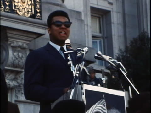 muhammad ali stands at a lectern with microphones pointed at him. he wears a dark blue suit and is alternating between reading prepared remarks and... - sport stock videos & royalty-free footage