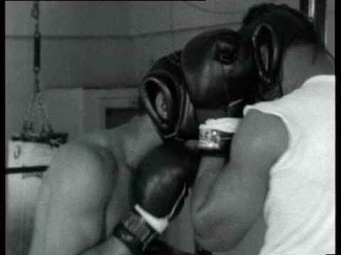 Muhammad Ali wearing protective headgear and gloves sparring with opponent in ring as he prepares for upcoming fight against Henry Cooper Muhammad...