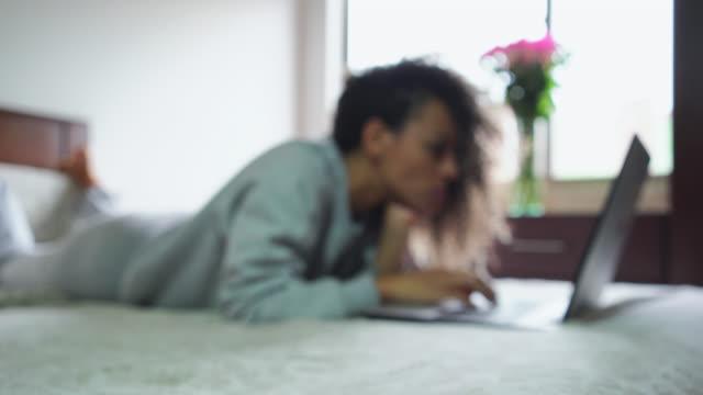 Mujer latina en la cama escribiendo en una computadora portátil