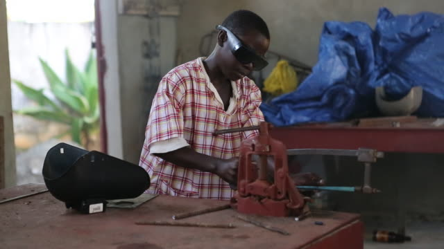 a multi clip of a young boy who is wearing protection glasses while he is working with a hacksaw in a metal workshop in pilate haiti - metal clip stock videos and b-roll footage