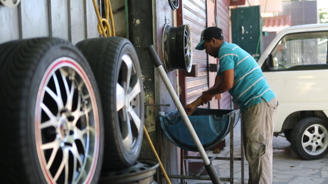 multi clip of a young man who is washing his oil smeared hands with a brush outside of a auto repair shop in a poor neighbourhood in santo domingo,... - lubrication stock videos & royalty-free footage