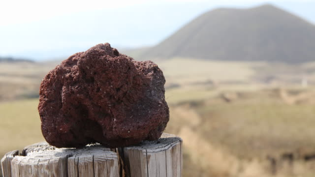 a multi clip showing a close up on a volcanic stone placed on a wooden fence with kome zuka in the background and little volcanic rocks at a side of... - caldera stock videos and b-roll footage