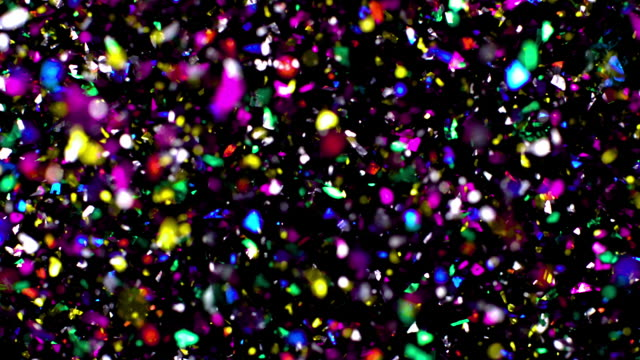 Multi colored confetti scattering in the air on black background, slow motion